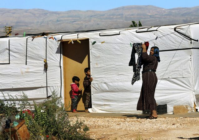 A Syrian refugee woman hangs laundry outside her tent at a Syrian refugee camp in the eastern city of Baalbek, Lebanon, Tuesday, June 20, 2017