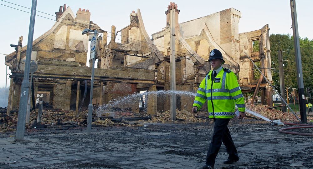 A policeman walks past the charred remains of the Reeves furniture store in Croydon, south of London, on August 9, 2011, following a third night of violence on the streets of London.