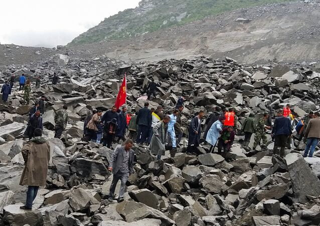 People search for survivors at the site of a landslide that destroyed some 40 households, where more than 100 people are feared to be buried, according to local media reports, in Xinmo Village, China June 24, 2017.