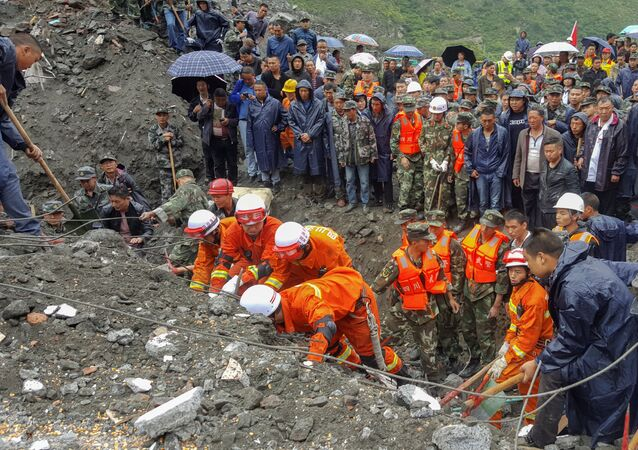 People search for survivors at the site of a landslide in Xinmo Village, Mao County, Sichuan province, China June 24, 2017