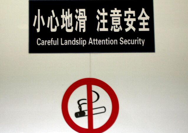 A sign at the entrance of a bathroom in a public building warns Careful Landslip Attention Security in Beijing on Aug. 8, 2006.