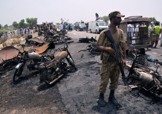 A soldier stands guard amid burnt out cars and motorcycles at the scene of an oil tanker explosion in Bahawalpur, Pakistan