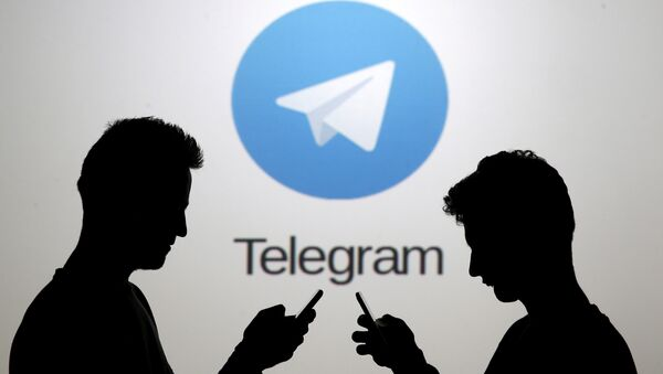 Men pose with smartphones in front of a screen showing the Telegram logo in this picture illustration November 18, 2015 - Sputnik International