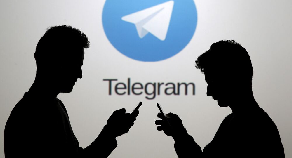 Men pose with smartphones in front of a screen showing the Telegram logo in this picture illustration November 18, 2015