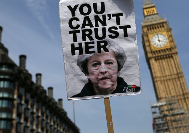 A placard showing a picture of Britain's Prime Minister Theresa May, saying You can't trust her is raised in front of the Elizabeth Tower, commonly referred to as Big Ben as protesters gather in Parliament Square after marching through central London on June 21, 2017.
