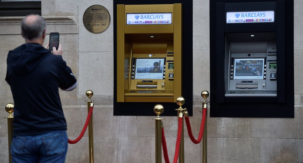 A man photographs a golden ATM, marking the location of the first 'hole in the wall,' which opened fifty years ago, in Enfield, Britain June 27, 2017.