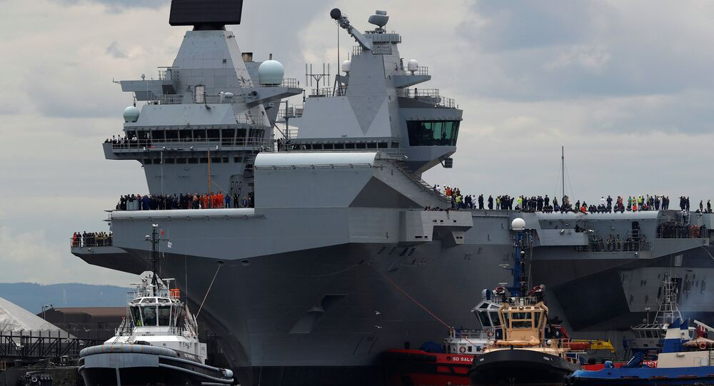 The British aircraft carrier HMS Queen Elizabeth is pulled from its berth by tugs before its maiden voyage, in Rosyth, Scotland, Britain June 26, 2017