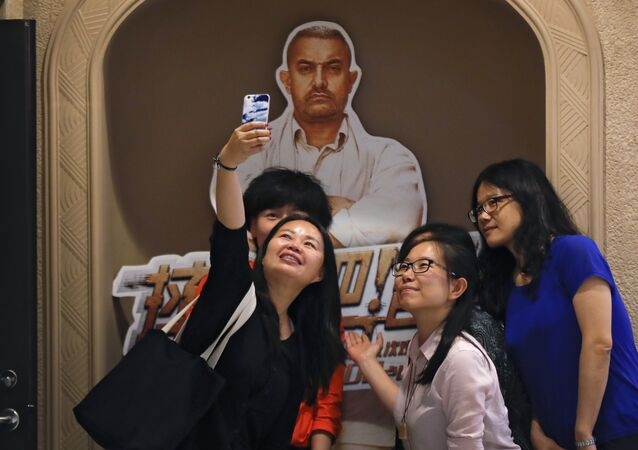 Chinese women take a selfie with a poster of Indian Bollywood blockbuster film Dangal on display at a cinema in Beijing.