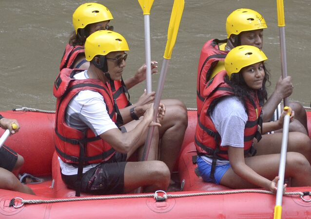 Former U.S. President Barack Obama, left, his wife Michelle, rear left, and daughter Sasha, right, raft on the Ayung River in Badung, on Bali island, Indonesia, Monday, June 26, 2017.