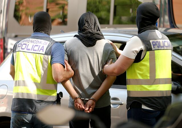 Police lead away a suspect from an apartment block during a raid in which they arrested a 32-year-old Moroccan they said was highly radicalised, in Madrid, Spain June 21, 2017