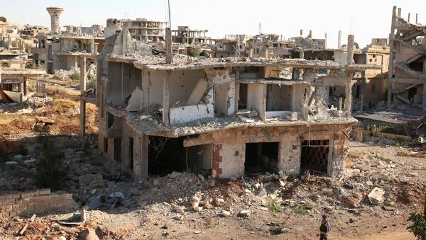 A rebel fighter walks past damaged buildings in a rebel-held part of the southern city of Deraa, Syria June 22, 2017 - Sputnik International