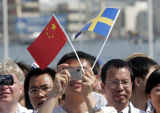 People equipped with flags and cameras greet Chinese president Hu Jintao on the arrival at Goteborg harbour to participate in the homecoming celebration of the sailing vessel Gotheborg on Saturday June 9, 2007
