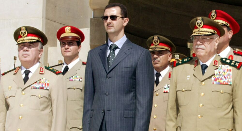 Syrian President Bashar al-Assad (C) new Defence Minister Hassan Turkmani (L) and former Defence Minister Mustafa Tlass attend a ceremony at the unknown soldier monument in Damascus, Syria October 6, 2003.