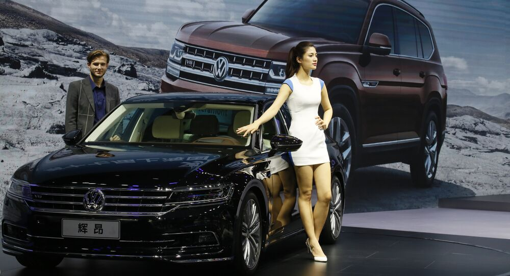 A female worker poses near cars from SAIC Volkswagen during the Auto Shanghai 2017 show at the National Exhibition and Convention Center in Shanghai, China, Thursday, April 20, 2017