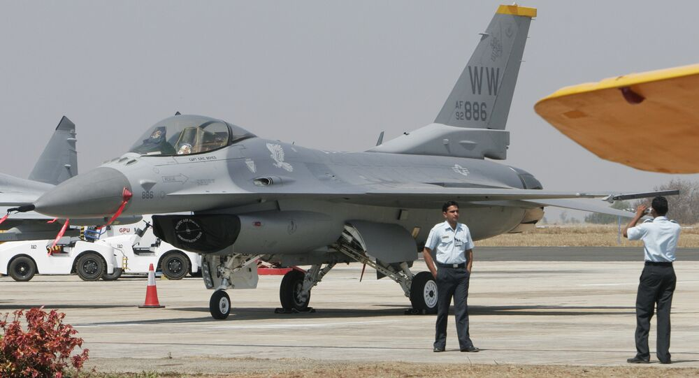 An Indian Air Force official poses for photographs with U.S. fighter aircraft F-16 parked at Yelahanka air base (File)