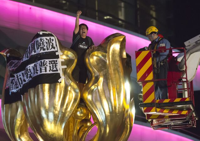 A police officer and a fireman try to remove a pro-democracy activist who shouts slogan and hangs a cloth that reads Release Liu Xiaobo unconditionally, Hong Kong people want genuine universal suffrage, on a giant flower statue bequeathed by Beijing in 1997 in Golden Bauhinia Square of Hong Kong Wednesday, June 28, 2017.