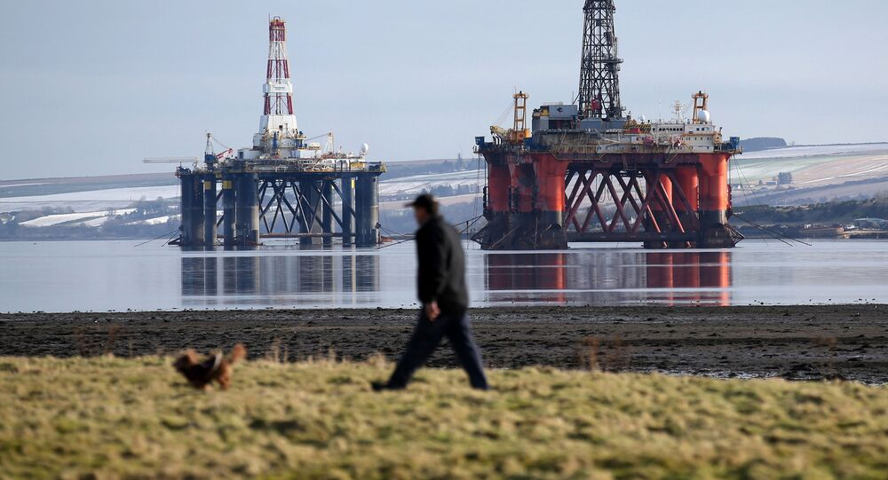 In this Monday Feb. 15, 2016 photo, a man walks past oil platforms laid-up in the Cromarty Firth near Invergordon in the Highlands of Scotland. North Sea oil has passed its zenith in terms of production as the recent plunge in energy prices forces oil companies to rethink investment in fields that were already in decline.