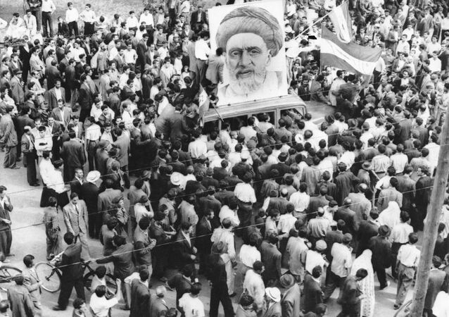In this Dec. 13, 1951 file photo, crowds of supporters of Prime Minister Mossadegh gather around a huge portrait of Iranian Mullah Kashani, one of the powerful backers of Mossadegh's regime, in Tehran. Once expunged from its official history, documents outlining the U.S.-backed 1953 coup in Iran have been quietly published in June 2017, by the State Department, offering a new glimpse at an operation that ultimately pushed the country toward its 1979 Islamic Revolution and hostility with the West.