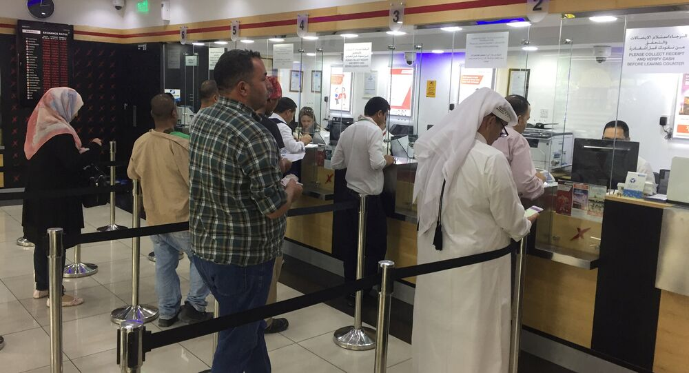 People exchange money from an exchange house in Doha, Qatar, June 11, 2017
