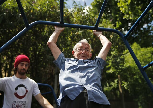In this Tuesday, June 17, 2014 photo, George Jackson, 85, an army veteran and former boxer swings on monkey bars as he participates at a parkour class for elderly people at a park in south London