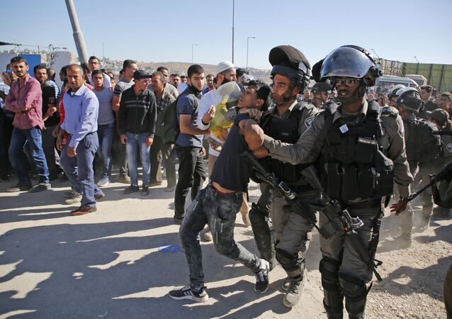 Israeli border police detain a Palestinian youth as crowds make their way through the Israeli Qalandia checkpoint, in the occupied West Bank between Ramallah and Jerusalem, to attend Friday prayer of the holy fasting month of Ramadan in Jerusalem's al-Aqsa mosque, on June 16, 2017