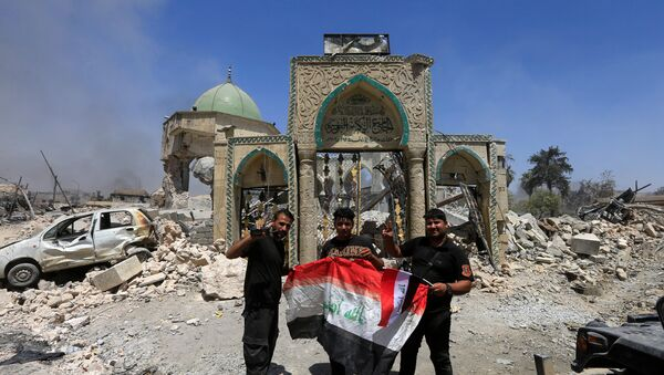 Members of the Counter Terrorism Service pose for a picture with an Iraqi flag in front of the ruins of Grand al-Nuri Mosque at the Old City in Mosul, Iraq, June 30, 2017 - Sputnik International