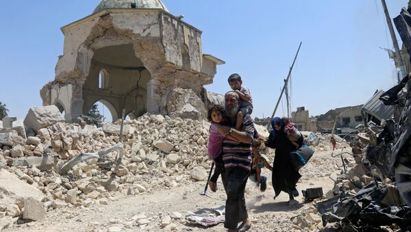 Displaced Iraqi civilians walk past the ruined Grand al-Nuri Mosque after fleeing from the Old City in Mosul, Iraq, June 30, 2017 - Sputnik International