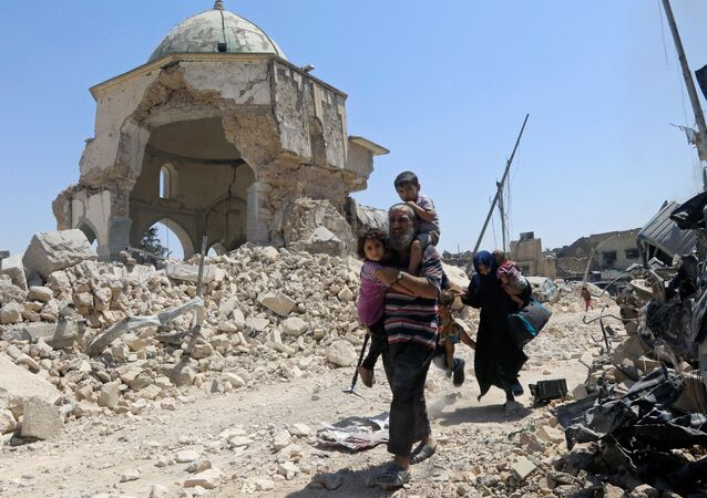 Displaced Iraqi civilians walk past the ruined Grand al-Nuri Mosque after fleeing from the Old City in Mosul, Iraq, June 30, 2017