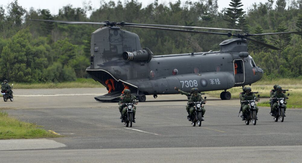 This file photo taken on May 25, 2017 shows armed Taiwanese soldiers riding on motorcycles next to a US-made CH-47 helicopter during the Han Kuang (Han Glory) life-fire drill, some 7 kms (4 miles) from the city of Magong on the outlying Penghu islands