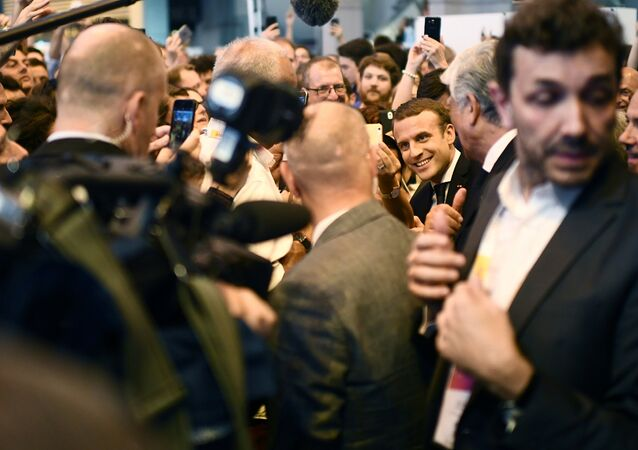 French President Emmanuel Macron (C,R) surrounded by journalists, meets people as he arrives at the Viva Technology conference dedicated to start-ups development, innovation and digital technology in Paris, France, June 15, 2017