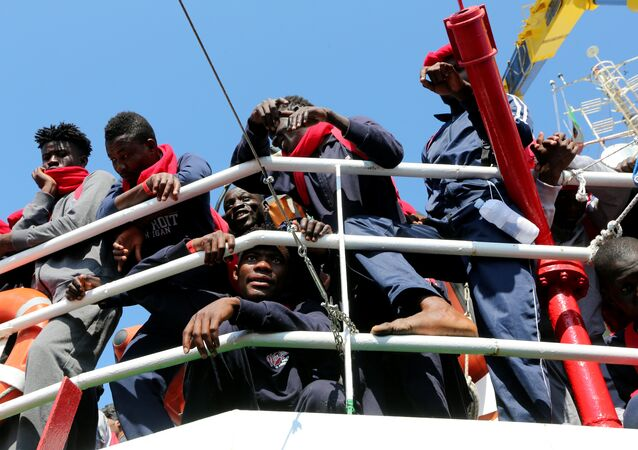 Migrants waits to disembark from the Vos Hestia ship as they arrives in the Crotone harbour, Italy, after being rescued by  Save the Children crew in the Mediterranean sea off the Libya coast, June 21, 2017