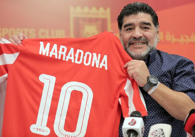 Former Argentinian footballer and manager Diego Armando Maradona holds a jersey of the football club Fujairah FC, bearing his name on the reverse, during a press conference where he was announced as the upcoming manager for the team, in the Gulf emirate of Fujairah on May 14, 2017