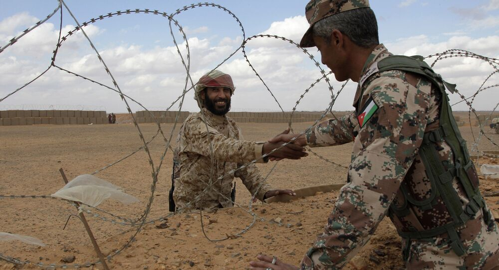 A member of the Syrian Tribes Army, left, that guards the Syrian side of the berm on the north eastern border with Jordan, shakes hands with a Jordanian soldier (File)