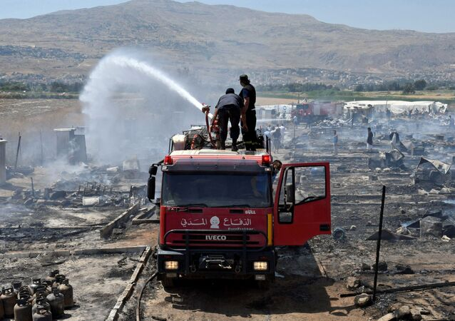 Civil defence members put out fire at a camp for Syrian refugees near the town of Qab Elias, in Lebanon's Bekaa Valley