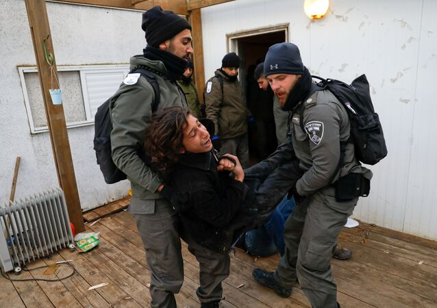 Israeli policemen remove a pro-settlement activist from a house during an operation by Israeli forces to evict settlers from the illegal outpost of Amona in the occupied West Bank February 1, 2017.