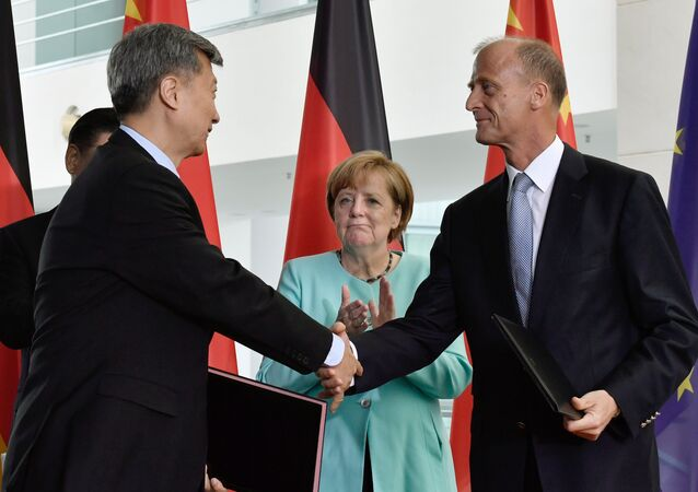 German Chancellor Angela Merkel (C) looks on as Tom Enders (R), CEO of the Airbus Group, shakes hands with a Chinese trading partner during a signing ceremony of German-Chinese business contracts at the Chancellery in Berlin