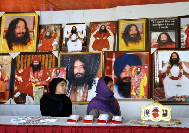 This file photo taken on December 14, 2014 shows Indian followers of deceased guru Ashutosh Maharaj sitting in front of posters bearing his image at a stall during a congregation at his ashram