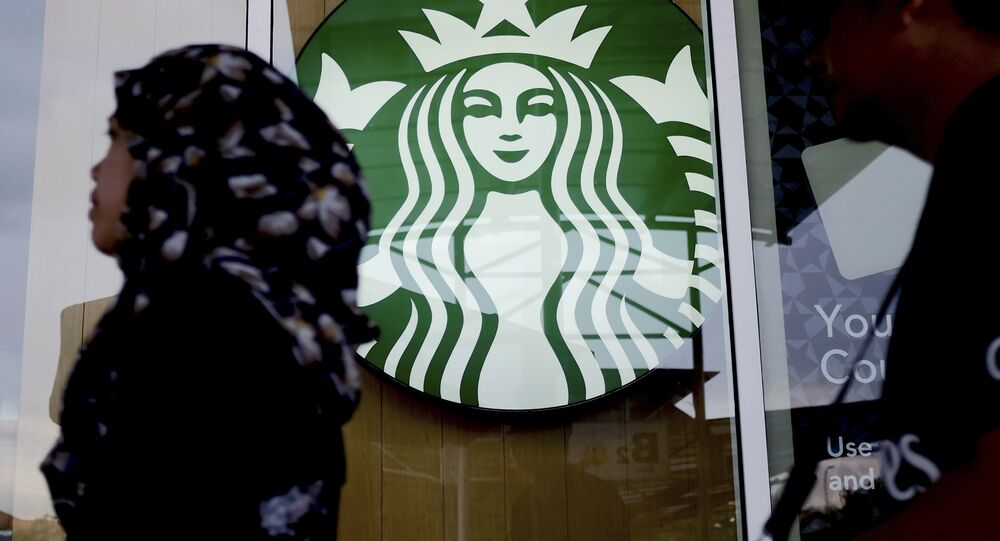 A Muslim woman walks past a Starbucks Coffee shop in Rawang outside Kuala Lumpur, Malaysia, Thursday, July 6, 2017.