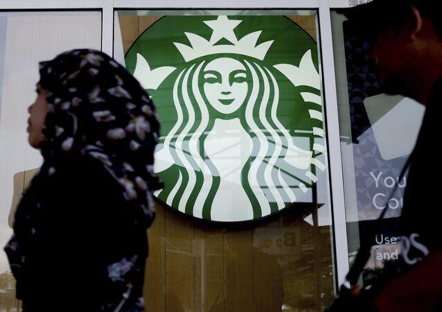 A Muslim woman walks past a Starbucks Coffee shop in Rawang outside Kuala Lumpur, Malaysia, Thursday, July 6, 2017.