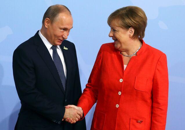 German Chancellor Angela Merkel greets Russian President Vladimir Putin as he arrives for the G20 leaders' summit in Hamburg, Germany July 7, 2017 (File photo).