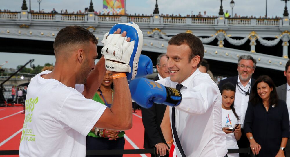 French President Emmanuel Macron (R) spars with a boxing partner in Paris, France, June 24, 2017