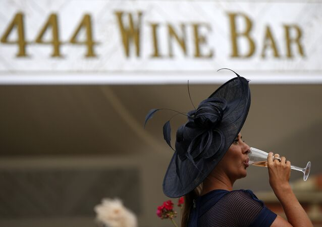 A racegoer drinks a glass of wine during Ladies day at Royal Ascot in Ascot, west of London on June 16, 2016.