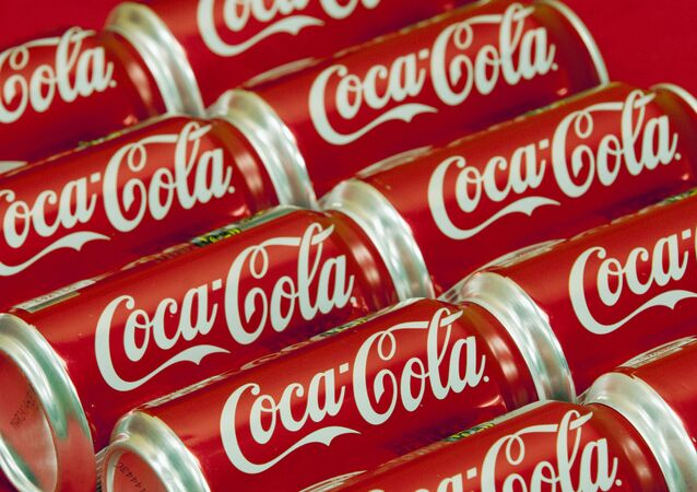 FILE - This July 15, 2013 file photo shows cans of Coca-Cola in Doral, Fla.