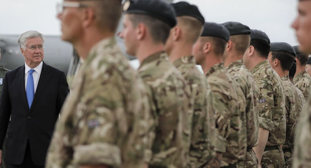 Britain's defense minister Michael Fallon reviews British military personnel at the Mihail Kogalniceanu air base, Romania, Wednesday, June 14, 2017.