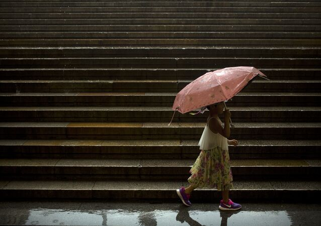 A girl carries an umbrella as she walks along steps leading to Tiananmen Square on a rainy day in Beijing, Thursday, July 6, 2017.