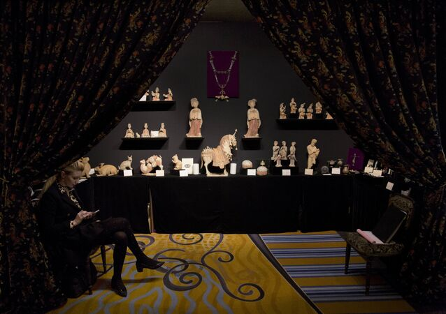 An exhibitor sits in a pottery antiquities stand before the doors open to the public at the fifth annual Mayfair Antiques and Fine Art Fair in London