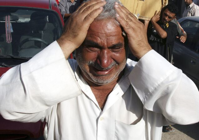 A man weeps for Saad Mozan, 42, who was killed in an overnight raid by US troops in the Shiite stronghold of Sadr City in Baghdad, Iraq on Monday, Sept. 24, 2007.
