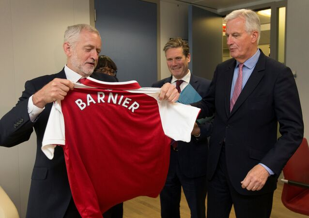 Britain's opposition Labour Party leader Jeremy Corbyn offers an Arsenal soccer team jersey to European Union's chief Brexit negotiator Michel Barnier during a meeting at the EU Commission headquarters in Brussels, Belgium, July 13, 2017.