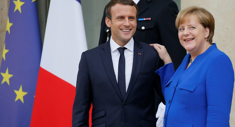 French President Emmanuel Macron (L) accompanies German Chancellor Angela Merkel following a Franco-German joint cabinet meeting at the Elysee Palace in Paris, France, July 13, 2017.
