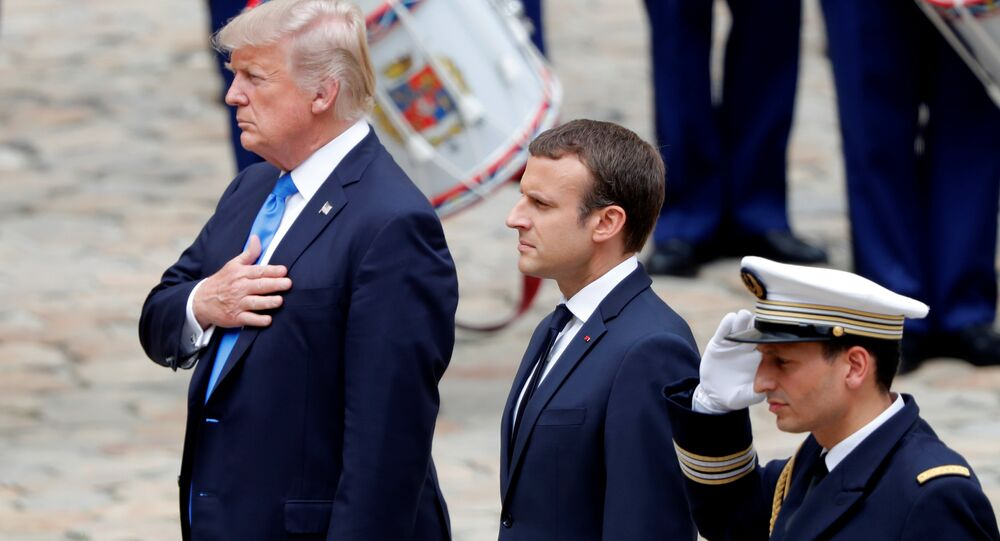 French President Emmanuel Macron and US President Donald Trump listen to national anthems during a welcoming ceremony at the Invalides in Paris, France, July 13, 2017.